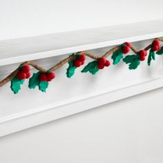 Artisans in Nepal hand roll felted wool to form the string of our unique garland with hanging holly clusters. Drape it across a mantel or table to add folksy flair to your holiday decor.