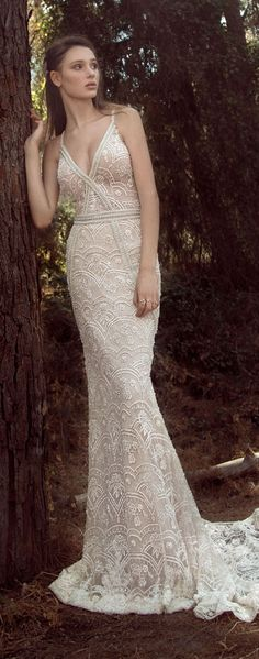 GALA 907. Slim fitted embroided ivory mermaid gown with a low front v-neckline and thin straps. This dress is handmade with appliques of crystals and pearls.