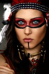 Close-up portrait of beautiful woman in native american costume with feathers