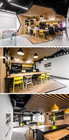 In the employee break room of this modern office, the area is split up into two sections, the first being the kitchen and dining area. Diagonal lines that outline the wood have been used to clearly define the area, while the wood slats and wood wall create a contrast to the black and yellow kitchen.
