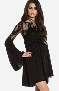 Fit and flare dress featuring a sheer lace bodice, half lace half fabric bell sleeves, an elasticized waist. Unlined. Slips on over head. Shown with our Seamless Cami. By For Love & Lemons.