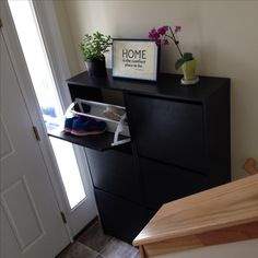 Small split level entryway with Ikea Bissa shoe cabinets and simple decor