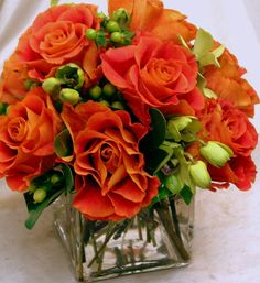This is a cube vase floral arrangement that features orange roses with accents of green hypericum berries.  See our entire selection at www.starflor.com.  To purchase any of our floral selections, as gifts or décor, please call us at 800.520.8999 or visit our e-commerce portal at www.Starbrightnyc.com. This composition of flowers is generally available for same day delivery in New York City (NYC). SQ118