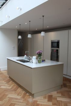 Pure handleless kitchen cabinetry from John Lewis of Hungerford. Gorgeous mix of grey and white painted cabinets and marble-look quartz worktops, paired with a modern oak herringbone floor. http://www.john-lewis.co.uk/map-showrooms/fulham/portfolio/pure-kitchen-in-fulham-