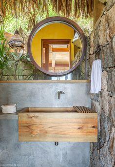 Lavabo com paredes de pedra, bancada de concreto e cuba de madeira.
