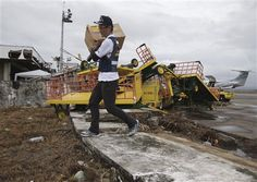 A member of the Japanese Disaster Relief Team carries goods as they arrive to assist survivors of Typhoon Haiyan in Tacloban, Leyte, central Philippines on Tuesday, Nov. 12, 2013. Japan has decided to donate $10 million to the Philippines for emergency aid to victims of Typhoon Haiyan. (AP Photo/Aaron Favila)