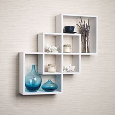 Decorative wall shelvf shows 3 boxes that intersect and connect with each other creating a geometric pattern with 6 openings. Hidden perforations secure to nails or screws, and allow for the piece to be hung either vertically or horizontally.