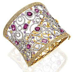 DIAMOND, COLOURED DIAMOND, SAPPHIRE AND RUBELLITE BANGLE.The oval openwork hinged bangle claw set to the front with round brilliant cut diamond set circular motifs highlighted with variously cut rubellites, coloured diamonds and variously coloured sapphires, to a pavé set yellow tinted diamond border, the rubellites and coloured diamonds together weighing approximately 12.96 carats and 11.66 carats respectively, mounted in 18ct gold, inner diameter approximately 65mm.