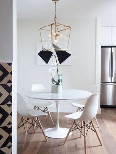 Modern geometric elements add visual interest to a small dining area in a modern kitchen centered around the marble tulip dining table