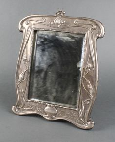 "Lot 516, A good Art Nouveau repousse silver dressing table mirror, decorated with king fishers among lilies and lily pads, Indistinct date letter 12"" x 10"", Est £300-600"