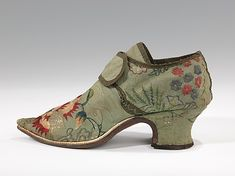 Shoe, 1720-1749, British, silk? This shoe in the classic shape of the period is a representative example of early 18th century domestic needlework in a popular Indian-inspired floral design. In some areas the embroidery has worn away, showing how the design was first drawn on the fabric in pencil. (c) The Metropolitan Museum of Art