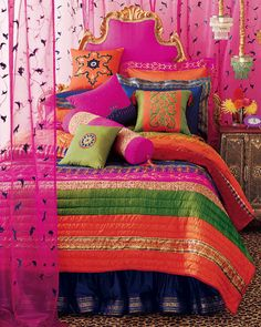 Bright and pretty quilt with a big pile of pretty pillows make for a very inviting bedroom