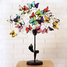 Table lamp made of black coloured aluminium wire, metal black base with an arum lily and a leaf, and multicolor butterflies made of vegetal