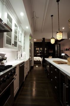 Suzie: Sleek two-tone galley kitchen with crisp white shaker cabinets with marble countertops ...
