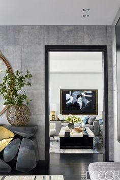 A beautiful gray living room features a mirror by Hudson Furniture and a stunning custom design cocktail table.