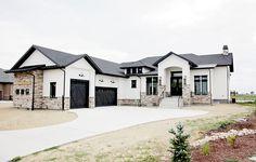 Modern rustic white farmhouse. Black doors. Black trim. Stone, board and baton and siding. Black metal roof. Black garage doors.