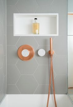 This bathroom features copper and marble fixtures next to light gray hexagon tiles