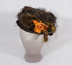 High Style Brown Velvet Hat With Elliptical Shape, Narrow Rolled Brim That Curls Up To Meet The Extravagantly Decorated Crown, Brim Is Covered With Matching Brown Ostrich Feathers, Brown Mink Pom-Poms And Velvet Pine Cones, Orange Velvet Rose Adds A Dash Of Color    c.1910