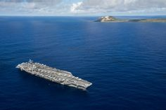 IWO TO, Japan (Sept 29, 2015) The Nimitz-class aircraft carrier USS Ronald Reagan (CVN 76) pauses to honor fallen service members from  the Battle of Iwo Jima while underway off the island of Iwo To, formerly known as Iwo Jima. This year marks the 70th anniversary of the end of World War II. Ronald Reagan's presence highlights how the relationship has grown between both countries who are committed to the peace, security and stability of the Indo-Asia-Pacific region. (US Navy)