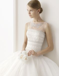 Rosa Clara Bridal: CESAR A strapless wedding dress with a fitted, geometric, beaded bodice ending at the dropped waist and a princess skirt of layered ruffles full of volume. Wear strapless or change your neckline from ceremony to reception with the embroidered butterfly, tulle sleeveless jacket.