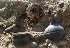 An excavated skull and artifacts lay unearthed at the sports complex where Peru's national soccer team practices in Lima, Peru, Tuesday, Feb. 26, 2013. According to Peru's Ministry of Culture, 11 pre-Inca tombs belonging to the Lima culture (200-700 AD) and Yschma (1100-1400 AD) were located inside the sports complex in the district of San Luis, where excavations started in Dec. 2012. Martin Mejia — AP Photo