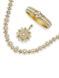 A seed pearl necklace and bangle suite, circa 1890. Necklace composed of floret links, suspending a snowflake pendant, set throughout with seed pearls; the cuff en suite.