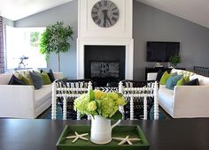 gray, brown, green living room | Living room with white couches and grey walls – by Tara Bussema