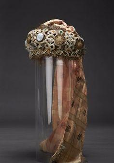 Конура - КОНУРА — головной убор просватанной девушки. Это обруч из бересты или проклеенного в не сколько рядов картона, обтянутый снаружи золотным или серебряным позументом, а изнут ри — ситцем или набойкой. К обручу прикреп лялся ажурный валик из проклеенного холста и нашитого на него шнура. На шнур и холст при креплялся бисер, цветные стекла в металличе ской оправе, овальные медальоны с росписью из эмали, подвески из бисера, брошки, пуговицы, цветочки из прокрахмаленного холста и др…