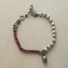 """FINE BALANCE BRACELET--Freshwater pearls, luminous as a storm-washed sky, join faceted rubies, red as embers, while a sage-colored pearl sings a solo. Sterling silver clasp and charms. USA. Exclusive. Fits 7-1/2"""" to 8"""" wrists."""