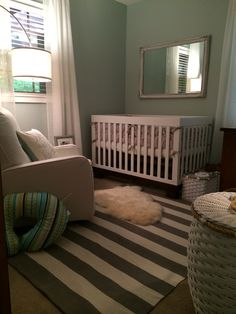 Gender neutral nursery with a hint of baby boy. Wall color -BM Palladian blue. Gray/White stopped rug - Homegoods. Sheer white plaid curtains - custom made. Crib - Babyletto Modo 3-in-1. Antique mirror DIY painted.