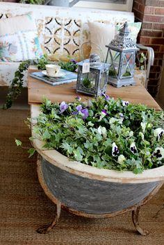 An old cast iron bathtub holds flowers and when topped with a board, serves as a coffee table, too...