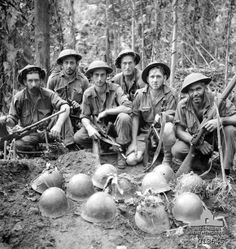 1942-11-23. New Guinea. Gorari. Most of the hand to hand fighting took place in the Gorari region, where one Australian unit killed and buried over 500 Japanese. The Japanese dead were buried in common graves, 5, 6, and up to 10 in one grave. Their steel helmets were placed on the top of the graves. In this photo is an Australian burying party.