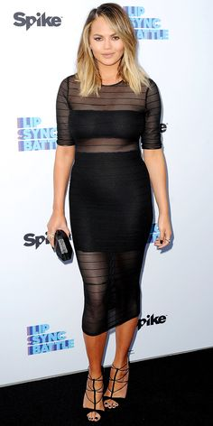 Chrissy Teigen in a sheer LBD with a bandeau and pencil skirt silhouette, accessorizing with a black clutch and delicate strappy sandals.