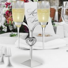 Two glass raindrop stem toasting flutes custom engraved with the bride's name and wedding date are suspended by a high polished silver plated toasting flutes holder with dangling heart centerpiece. Wedding Toasting Glasses, Wedding Flutes, Toasting Flutes, Head Table Wedding, Wedding Reception Decorations, Wedding Ideas, Wedding Stuff, Wedding Things, Event Planning Tips