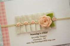 This little ruffle headband is softly pleated in an ivory fabric with dainty trim and a wool felt flower in pale peach. It is attached to a skinny
