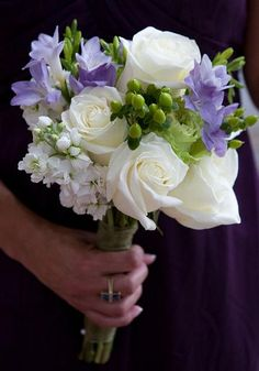 #bouquet featuring white roses and stock with accents of green berries and purple freesia