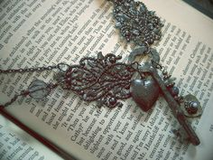 Beautiful antique skeleton key with charms and locket, connected with intricate filigree. Rustic and dark.