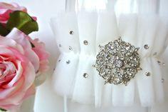 "Custom Garter designs for La Gartier bride Chelsea Petro. White Layered Tulle with over one hundred tiny swarovski crystal rhinestones. Center ""Roman"" crystal rhinestone brooch."