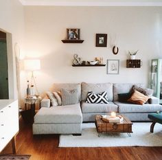 Light colors yet still cozy. Like the shelves and variety of items hanging above the couch.