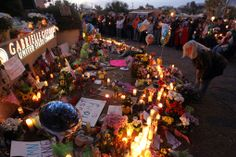 """People gather at the grassroots tribute memorial at Congresswoman Gabrielle Giffords' office in Tucson following the tragic shootings of January 8, 2011. Congresswoman Giffords and 18 others were shot at her """"Congress on Your Corner"""" event at a Safeway store in Tucson, Arizona; six people perished in the attack."""