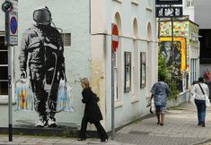 A woman walks past some graffiti art on a building in the Stokes Croft area of Bristol, southwest England, September 9, 2009.