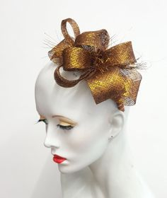 I have used a gold metallic and sinamay fabric to form loops for this simple fascinator. The fabric has also been shredded and added for extra embellishment. It is mounted onto a wide headband covered in coordinating brown and gold ribbon. This can be worn to either side of the head. Handmade by me in the UK and ready to ship. Any questions please ask I am always happy to help