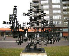 Bewogen scherm van André Volten (1968 & 2009) Voor het gemeentehuis in Hoogezand: Waar je ook bent in dit beeld, je zult verdwalen. toch hoef je nooit bang te zijn de weg kwijt te raken. Overal is lucht en helderheid. Overal zijn ingangen die op hetzelfde moment uitgangen zijn.