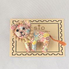 リバティプリントを使用したライオンのブローチです。サイズ:横8.5㎝×縦5.5㎝素材:表地→リバティプリント(綿)、裏地→フェルト、ビーズ、刺繍糸、ブローチ金具※尻尾を引っ張ると取れることがございますのでご注意ください。