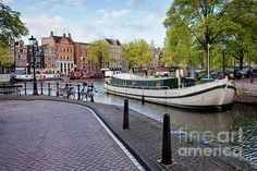 City of Amsterdam cityscape, houseboats on Groenburgwal canal and Amstel river, Netherlands, North Holland province.