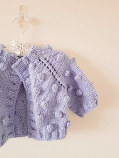 This dreamy baby cardigan will be a must have in your little ones closet. Features squishy bobbles and a top-down design so no seaming is required. Crochet Poncho With Sleeves, Baby Cardigan Knitting Pattern Free, Crochet Baby Sweaters, Baby Sweater Patterns, Knitted Baby Cardigan, Baby Knitting Patterns, Knitting Designs, Baby Patterns, Knitting Projects