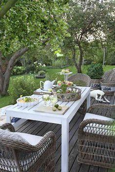 terrasse en bois avec coin repas aménagé avec des fauteuils en osier et une table en bois blanche