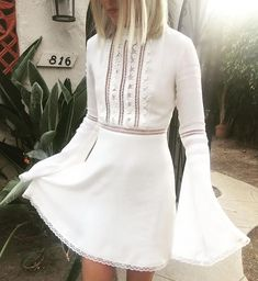 """The Willow Bell Sleeve Dress by For Love and Lemons features mock neckline with lace contrast, tiny ladder cutouts on the bodice, long bell sleeves, and floral trim. ImportedDry Clean OnlyRayon BlendFit Guide:Model is 5ft 7 inches; Bust: 32"""", Waist: 24"""", Hips: 34""""Model is wearing a size XSRelaxed FitShoes Featured Not Available For Purchase"""