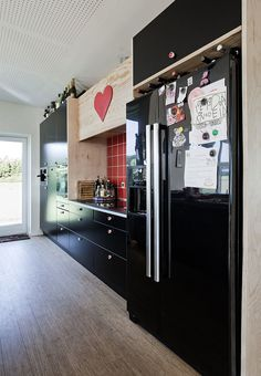 Black kitchen from Ikea with red tiles and plywood. A heart-room of the house.