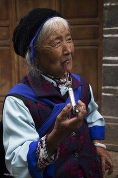 Naxi lady smoking opium in the street of Baisha, near Lijiang, Yunnan, China.